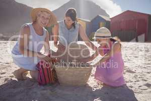 Multi-generation family by picnic basket on sand at beach
