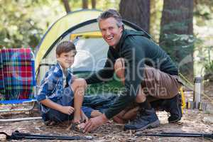 Cheerful father and son kneeling by tent in forest