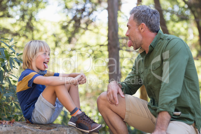 Father and son sticking out tongue while sitting in forest
