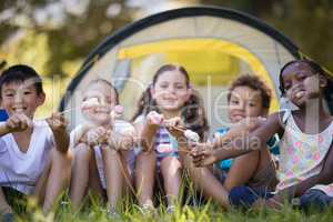 Happy friends showing candies while sitting by tent at campsite