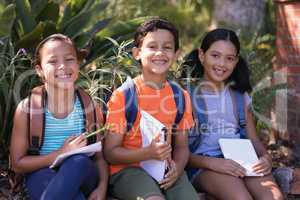 Smiling friends with books and digital tablets sitting on retaining wall