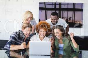 Cheerful business people looking at laptop