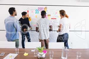 Business colleagues standing by whiteboard