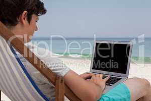Man using laptop at beach