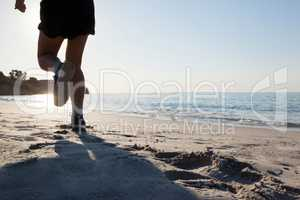 Man jogging on beach against blue sky
