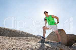 Exhausted man taking a break after jogging on beach