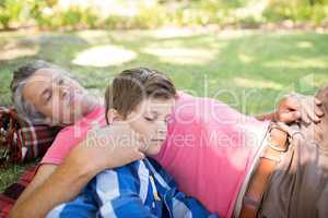 Father and son sleeping on picnic blanket in park