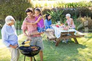 Happy girl, father and grandfather preparing barbecue