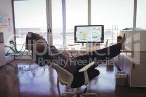 Young businessman resting on chair in creative office