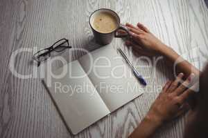 Hands of businesswoman by notebook and coffee cup on table
