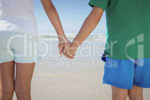 Mid section of siblings holding hands at beach