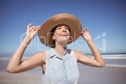 Happy woman wearing sun hat at beach