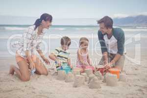Happy family making sand castle