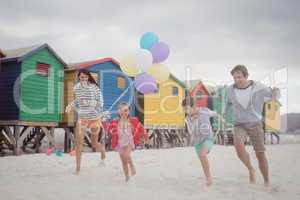 Happy family holding balloons while running at beach