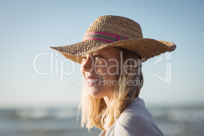 Happy woman looking away while wearing sun hat at beach