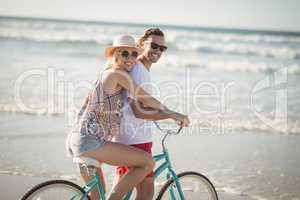 Smiling couple riding bicycle at beach