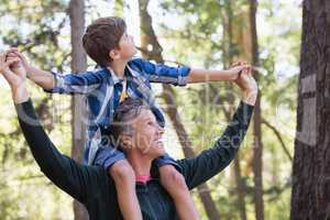 Father carrying son on shoulders while hiking in forest