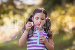 Girl blowing bubbles with wand on sunny day in forest