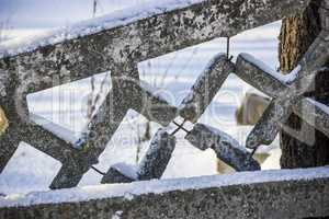 damaged concrete fence in winter