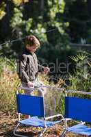 Little boy holding fishing net by chairs
