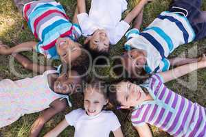 Smiling friends lying on grassy field in forest