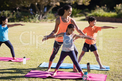 Female instructor examining children praciting Virabhadrasana II pose