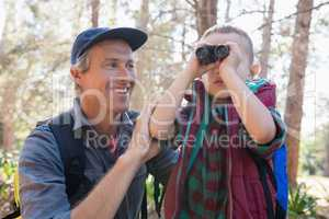 Happy man watching son looking through binoculars