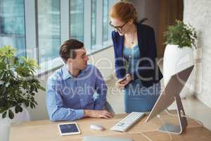 Executives discussing over mobile phone at desk