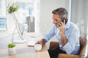 Executive talking on mobile phone at desk