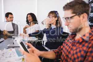 Businesswoman drinking water while sitting with colleagues