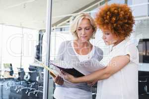 Businesswomen discussing over file in balcony