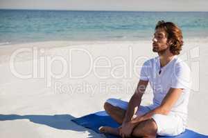Man with eyes closed meditating at beach