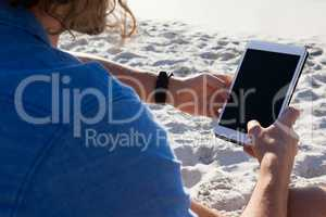 Man using digital tablet on the beach