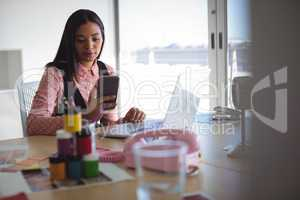 Young businesswoman using mobile phone at office desk