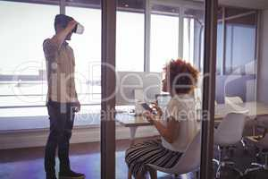 Businessman using VR glasses with businesswoman in office