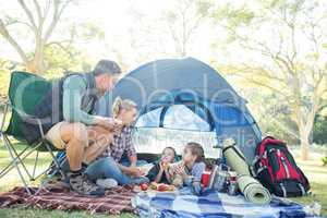 Family interacting while having snacks outside the tent