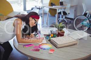 Businesswoman working while leaning on desk at office