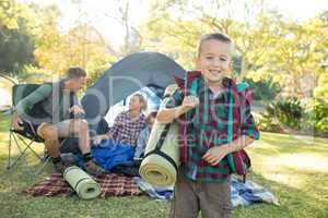 Boy holding a rolled mat while family sitting in the tent