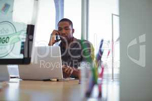 Businessman talking on phone while working in creative office