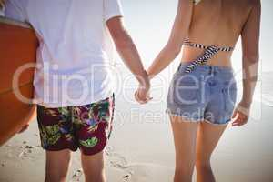 Mid section of couple holding hands at beach