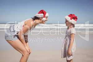 Cheerful woman with daughter wearing Santa hat at beach
