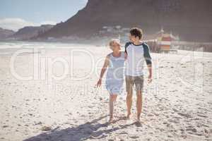 Young man with his mother walking on sand at beach