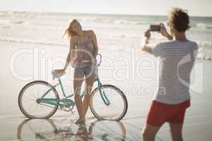 Smiling woman standing by bicycle while man photographing her at beach