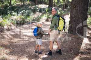 Smiling father and son carrying backpack while hiking in forest