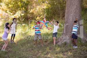 Friends cheering for blindfolded boy hitting pinata hanging on tree