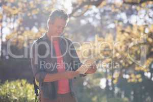Mature man reading map in forest