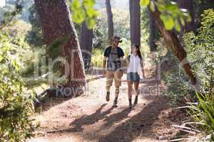 Happy couple hiking on trail in forest