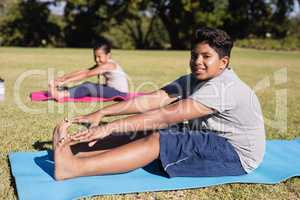 Portrait of boy touching toes during yoga glass