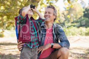 Father watching at boy looking through binoculars