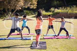 Instructor teaching kids Virabhadrasana II on mat